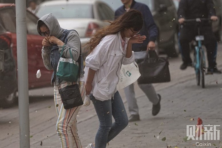 Office workers hide their faces while walking in the wind and dust near the Tuanjiehu subway station in Beijing's Chaoyang district on Thursday.  Photo: Liang Yingfei/Caixin