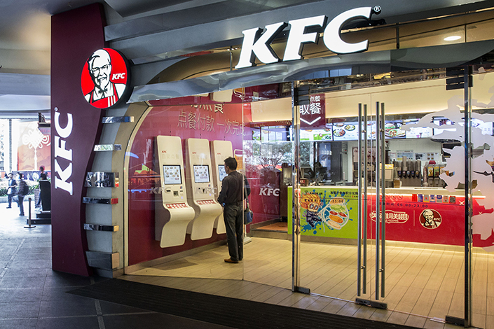 Yum China Holdings Inc., operator of the KFC and Pizza Hut fast food chains in China, said it will buy control of takeout delivery service Sherpa's. Above, a KFC custormer orders from a kiosk inside a restaurant in Shanghai in October 2015. Photo: Visual China