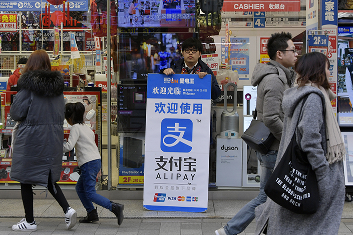 Ant Financial Services Group is forging partnerships in Asia, Europe and the U.S. in an ambitious bid to connect its payment service, Alipay, with more customers and merchants globally. Above, a store employee holds a billboard promoting Alipay in Akihabara area of Tokyo on Jan. 29. Photo: Visual China