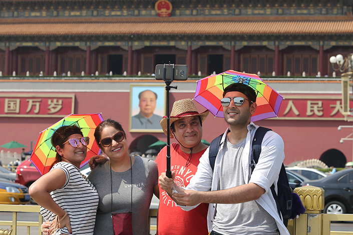 Overseas tourists visit Beijing's Tiananmen Square. Investment in China's tourism sector grew 29% in 2016 year-on-year. Photo: IC