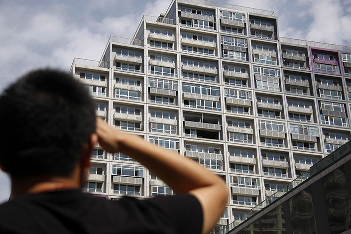 A pedestrian looks at a commercial property in Beijing on Aug. 25, 2013. Prices of commercial properties were 40%-60% lower than for residential properties. Numerous buyers who were not eligible to buy ordinary homes purchased residences converted from commercial properties. Photo: IC