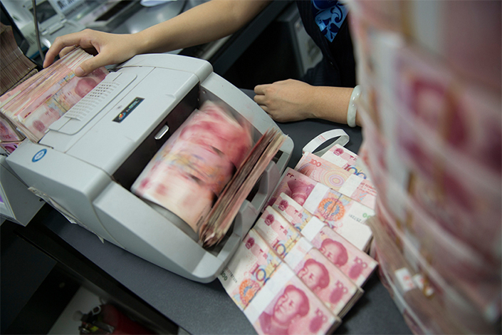 A clerk counts RMB banknotes with a counting machine in a bank. Photo: IC