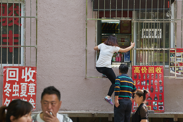 A grocery store employee climbs back in a store near Yaojiayuan Road in Chaoyang district, Beijing after handing a customer a bottle of water, on April 30. The original storefront was sealed during a government crackdown on illegal renovations of residential buildings. Photos: Liang Yingfei and Ma Minhui