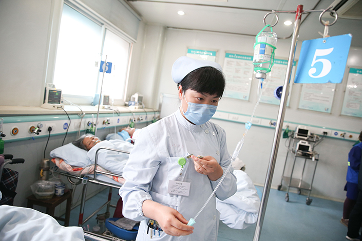 Nurse Li Ying helps patients replace their intravenous drips in the ward of a community health service center, in Minhang, Shanghai, China, on May 12. Poor pay and violence have led to a shortage of nurses in China. Photo: IC