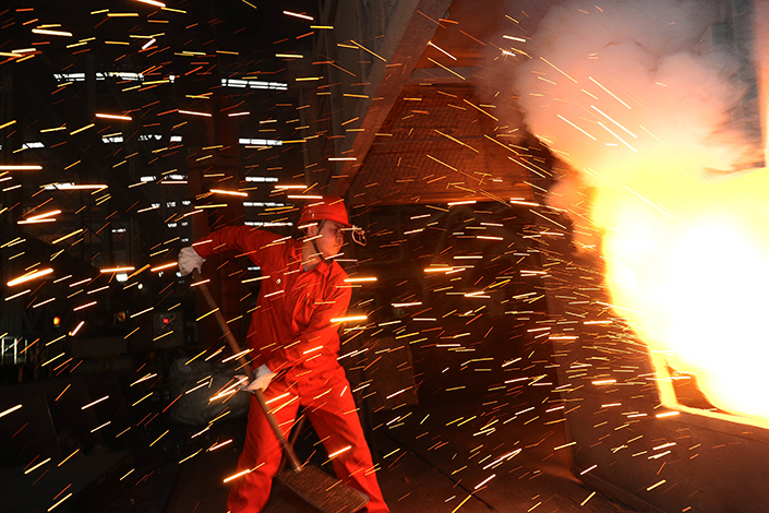 A worker adds deoxidizers to a steelmaking furnace in a factory of Dalian Iron and Steel Company, in Dalian, Liaoning province, China, on March 27. Photo: Visual China.