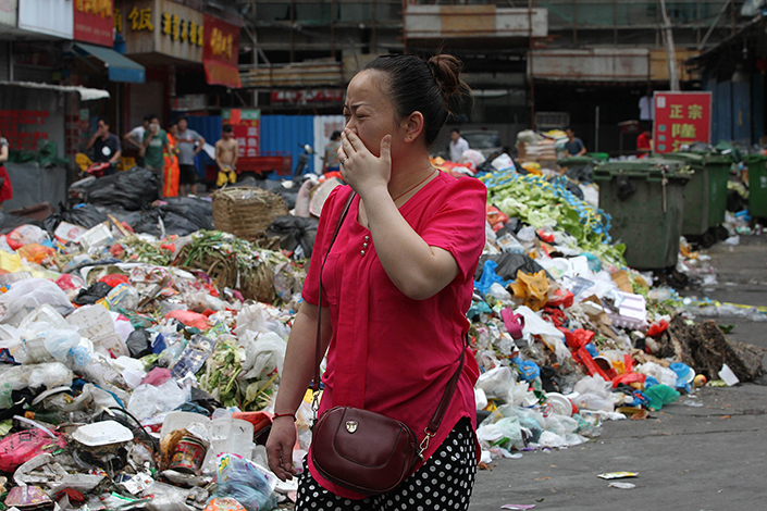 A pedestrian covers her nose when walking through a street filled with garbage in Baoan, Shenzhen, Guangdong province, on Aug. 29, 2014. Photo: Visual China