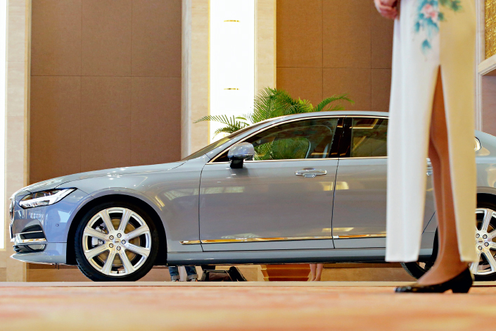 A hostess stands next to a Volvo S90, which is displayed at a panel discussion about self-driving cars at Diaoyutai State Guesthouse in Beijing, China, on April 7, 2016. Photo: Visual China