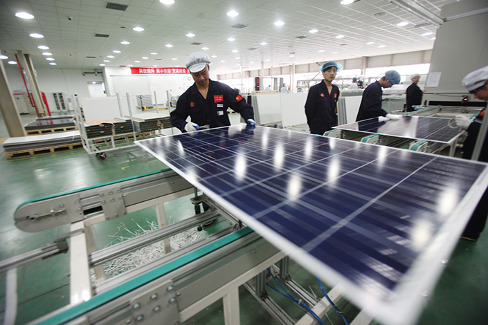 Yingli Green Energy Holding Co. Ltd. has become the latest Chinese solar-panel maker to withdraw from an agreement with the EU designed to avoid anti-dumping tariffs. Above, Yingli employees work on a manufacturing line in Tianjin in March 2013. Photo: IC