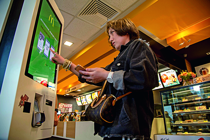 A fast-food customer places an order at an electronic kiosk, which allows payment through WeChat.