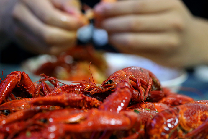 Production of farmed crawfish between 2007 and 2016 tripled, the Ministry of Agriculture said in a report released on Monday. Above, seafood customers shell crawfish in a restaurant in Hauian, Jiangsu province, on Saturday. Photo: IC