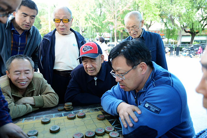 Retirees play chess in a Qingdao park. China's national reserve to cover coming shortfalls in retiree benefits posted its lowest return in five years. Photo: IC