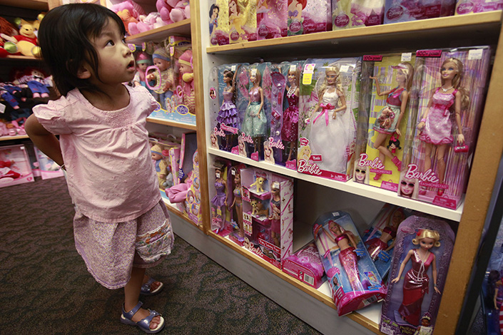 Mattel Inc. has announced a new joint venture to create play clubs in China with local private equity giant Fosun Group. Above, a 3-year-old girl examines Mattel-made Barbie dolls in a Palo Alto, California, toy store in July 2010.  Photo: IC