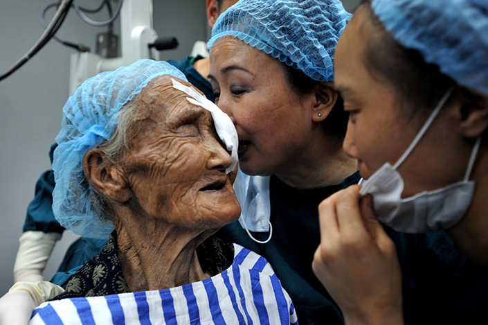 A 109-year-old woman celebrates her successful cataract surgery with nurses, in an Aier eye hospital in Guiyang, Guizhou province, on July 15, 2011. Photo: IC