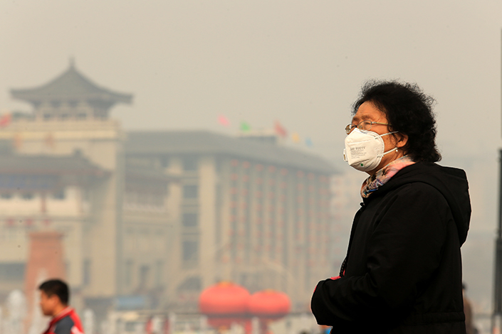 Seven people, including two former heads of district environmental protection offices in Xi'an, were sentenced to prison for over a year for tampering with air-quality monitoring equipment and falsifying readings in Shaanxi province's capital. Above, Xi'an residents brave the air pollution on Feb. 15.  Photo: Visual China