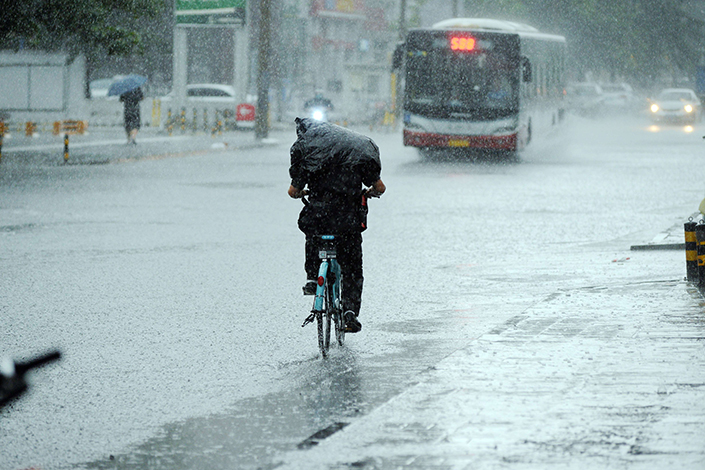 A downpour since Thursday has led to hundreds of flight cancellations in Beijing. Above, heavy rain and booming thunder have driven away most of the traffic in Beijing's Haidian district on Friday morning. Photo: Visual China