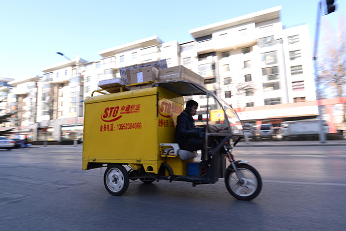 Chinese netizens have been debating an online post by an STO Express customer, who said that a company deliveryman hit her on the head with a rock after she complained to STO that her parcel was missing after the deliveryman said she had signed for it. Above, an STO deliveryman, who is not the one accused, rides through Beijing on Feb. 8, 2015. Photo: Visual China
