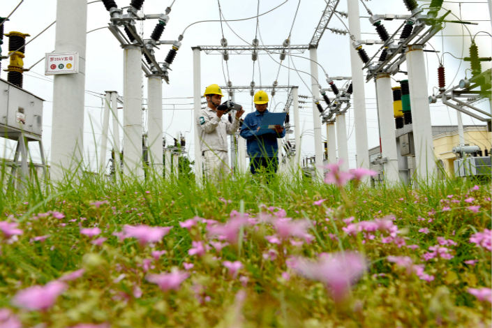 A central government pilot program has cost State Grid Corp. billions of yuan of revenue  in the first half of the year. Above, State Grid technicians check circuits at the Luolou transformer substation in Xiayi county, Henan province, on June 4. Photo: Visual China