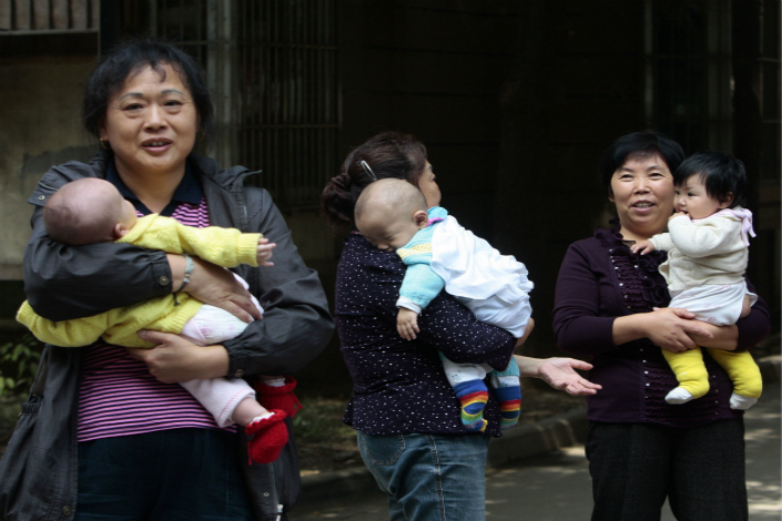 Academics warn that working mothers may opt to have fewer children if their parents retire later because so many Chinese grandparents help raise their grandchildren. Above, seniors look after children in October 2011 in Nanjing, Jiangsu province. Photo: Visual China.