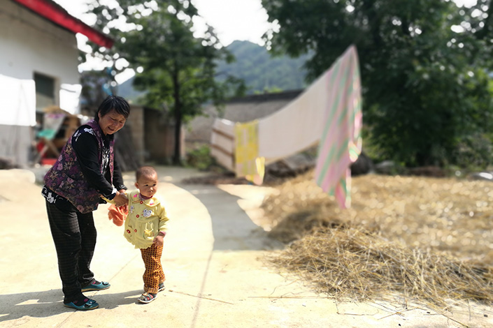 Qin Jie recently quit his position as head of poverty relief in the Qinba area of western China, citing frustration with government red tape and villagers who tried to take advantage of the system.  Above, a woman and child are seen in a Qinba village. Photo: Huang Shulun/Caixin