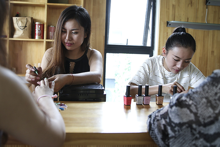 The Caixin China General Services Business Activity Index fell to 51.6 in June from a four-month high of 52.8 in May. Above, manicurists do customers' nails at a home in Beijing in July 2014. Photo: Visual China