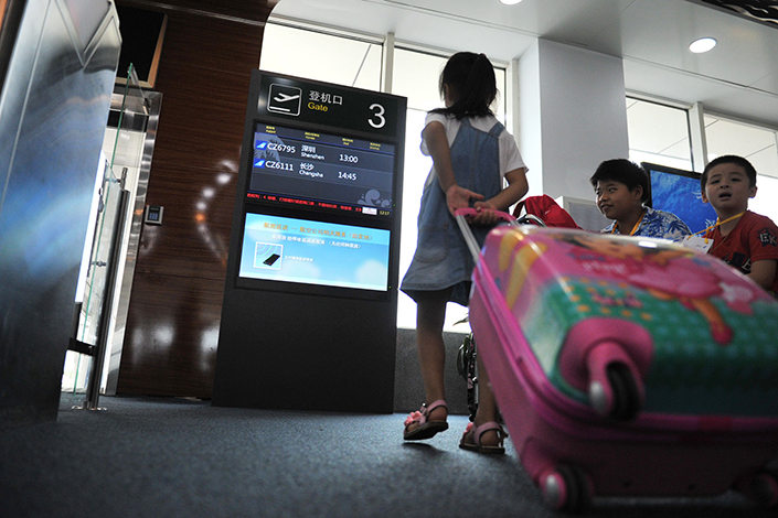 A girl boards a plane at Hainan's Meilan International Airport in Haikou, Hainan province, on Aug. 28, 2016. Photo: Visual China