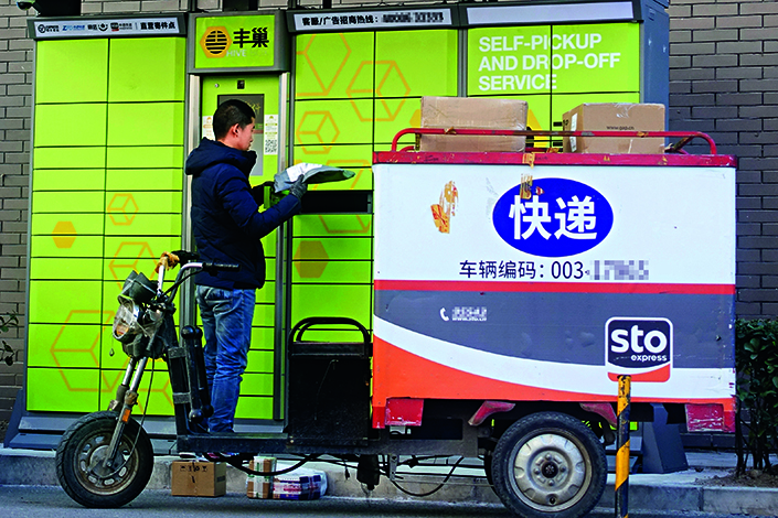 Banks of lockers have been appearing around Chinese cities as places to drop off and pick up packages on the last leg of delivery, saving couriers money and customers time. Above, a YTO Express deliveryman puts packages into a HiveBox locker in Beijing's Chaoyang district on March 5. Photo: Visual China.