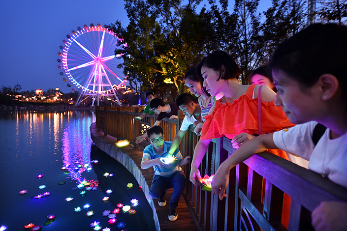 People float lanterns in a lotus shape at Chao Lake in Wanda-owned Hefei Theme Park in Anhui province, on July 23, 2016. Dalian Wanda Group is selling its chain of mega-resorts to real estate company Sunac China Holdings Ltd. for $9.27 billion. Photo: Visual China