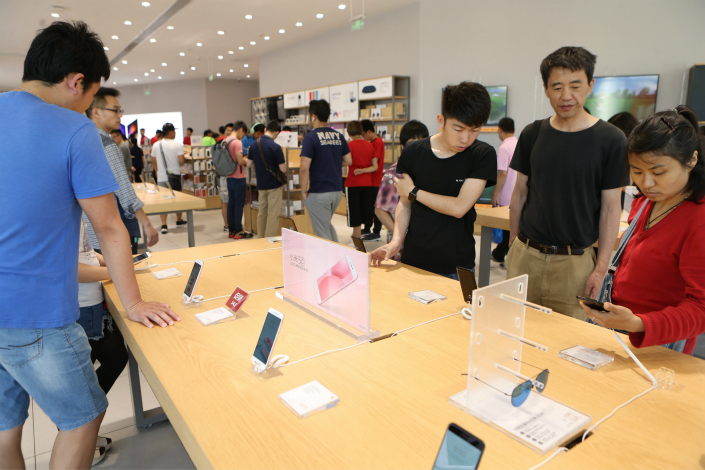 Xiaomi Inc. says its second-quarter sales jump resulted in part from integrating traditional brick-and mortar stores into its business model. Above, consumers shop at a Xiaomi store in Shanghai on May 28. Photo: IC