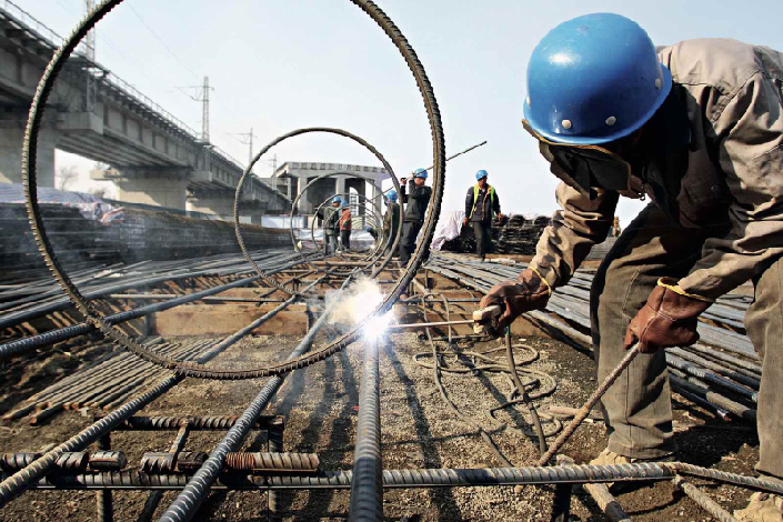 Loopholes in procurement rules have allowed officials to hide borrowing made to fund investment projects. Above, a worker welds a steel frame on March 17 for a bridge under construction on the Songhua River in Harbin, Heilongjiang province. Photo: Visual China