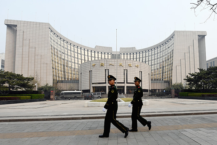 Soldiers walk by the People's Bank of China in Beijing on March 19. Photo: Visual China