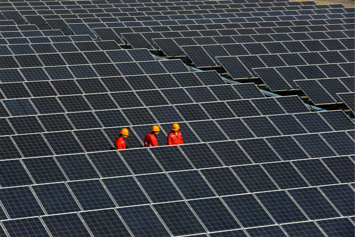 Workers examine photovoltaic panels that have been installed in Tongxiang, Zhejiang province on Dec. 18, 2014. Photo: Visual China
