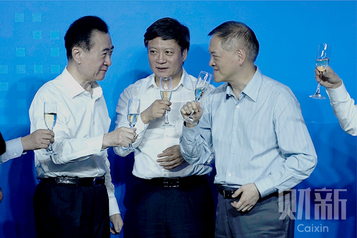 Wanda Group's planned sale of 13 theme parks and 76 hotels to Sunac China Holdings Ltd. was changed to include another buyer, R&F Properties, which will purchase the hotels instead of Sunac. Above, Chairman Wang Jianlin (left), Sunac Chairman Sun Hongbin (center) and R&F Properties Chairman Li Silian toast the deal's signing ceremony in Beijing on Wednesday. Photo: Yang Yifan/Caixin