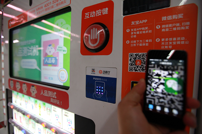 New Hua Du, with a market value of 5.7 billion yuan, is smaller than its new subsidiary Ubox, which has a market value of 6.5 billion yuan. Above, a customer scans a payment QR code on a Youbao vending machine in Beijing in May 2014. Photo: Visual China