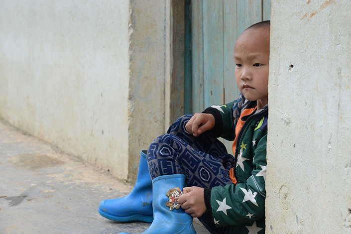 A boy sits in front of a door in Hechi, Guangxi, on April 20. The boy is one of 200 students at Shang Zhen primary school, where most of the children have parents who have left for work in China's bigger cities. Photo: Visual China