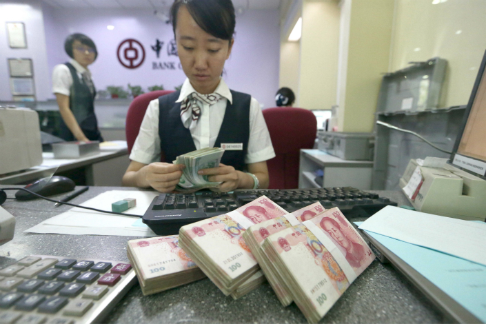 The combined debts of banks and other deposit-taking institutions fell to 71.2% of gross domestic product (GDP) at the end of March from 72.4% at the end of 2016. Above, a cashier counts money at a bank at Taiyuan, Shanxi province on July 17. Photo: Visual China