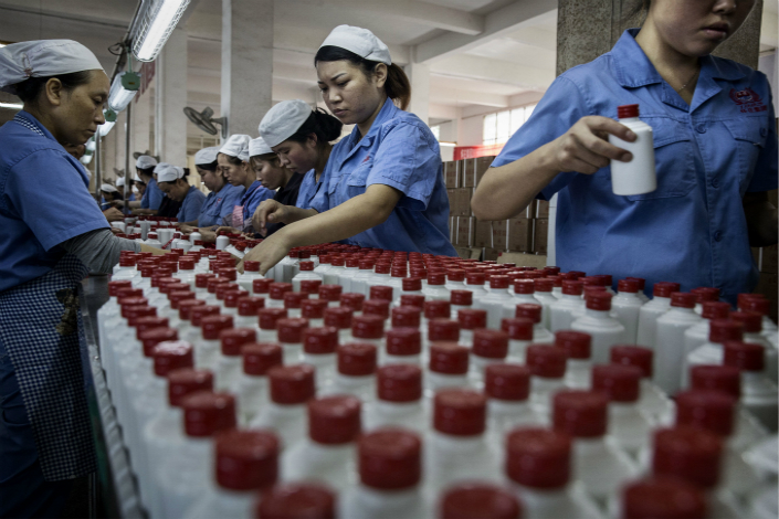 As business-related drinking has made a comeback in China, the stock price of baijiu-maker Kweichow Moutai Co. has continued to climb. Above, workers arrange bottles of baijiu at the Kweichow Moutai plant on Sept. 22 in Maotai, Guizhou province. Photo: Visual China