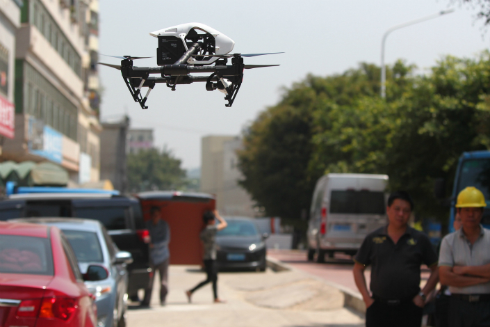 Guangzhou has become the latest Chinese city to enact regulations that tighten rules governing the use of drones. Above, law-enforcement personnel use a drone to patrol in Longgang district in Shenzhen, on April 15, 2015. Photo: Visual China