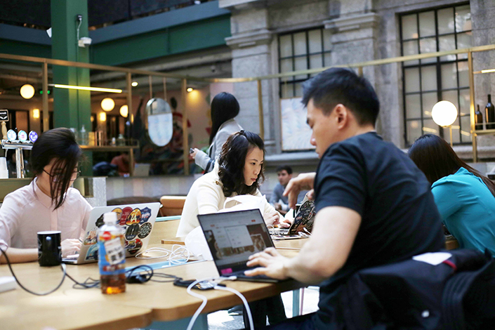 WeWork has split off its China operation into a separate company, with new investors Hony Capital and SoftBank as minority stakeholders. Above, people work at a WeWork workspace, where employees from different companies share space and resources, in Shanghai, on Feb. 28. Photo: IC