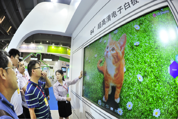 LG has announced it will build a facility to produce large-panel organic light-emitting diode displays in Guangzhou, Guangdong province. Above, an LG employee displays an 84-inch interactive whiteboard at the Guangzhou Pazhou International Exhibition Center in Guangzhou in August 2013. Photo: Visual China