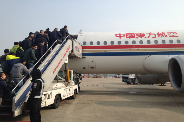 In separate deals, China Eastern Airlines Corp. Ltd. will buy 10% of Air France-KLM, while Air France-KLM will sell a 10% stake to Delta Air Lines Inc. Above, passengers board a China Eastern Airlines jetliner at Nanjing Lukou Airport in February 2015. Photo: Visual China