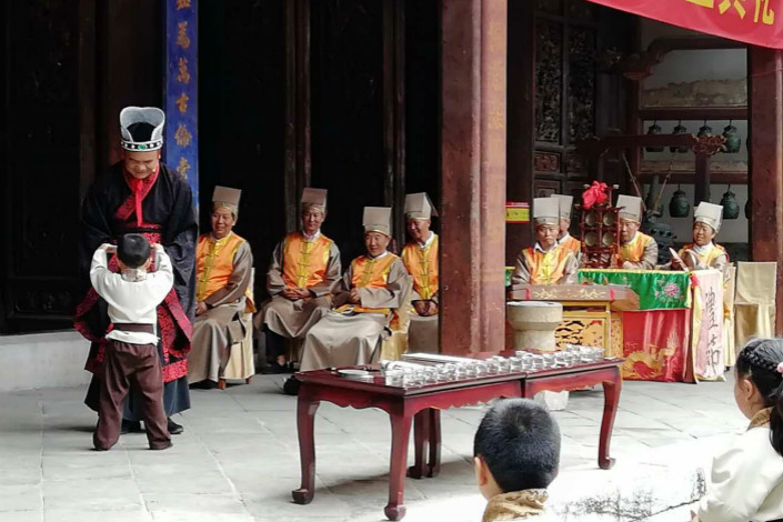 A preschooler gets ready to bow and receive a graduation certificate from his teacher during a ceremony at the Confucian temple in Jianshui county, Yunnan province. Both are dressed in traditional Chinese clothes. Photo: Yang Ge/Caixin