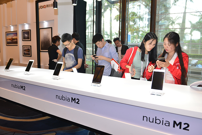 ZTE Corp. will retain less than 50% of Nubia after selling 10.1% of its stake in the higher-end smartphone brand. Above, customers try out Nubia's M2 smartphone model at a launch event in Shenzhen, Guangdong province, on March 21. Photo: IC