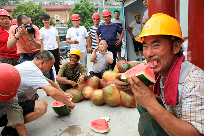 A study that shows the lack of success that migrant workers have finding employment if they return home appears to bode ill for government efforts to encourage rural farmers to remain in their villages. Above, a migrant worker eats watermelon provided by volunteers who showed their appreciation for the migrants' work at a construction site, in Xuchang, Henan province, on July 16. Photo: IC