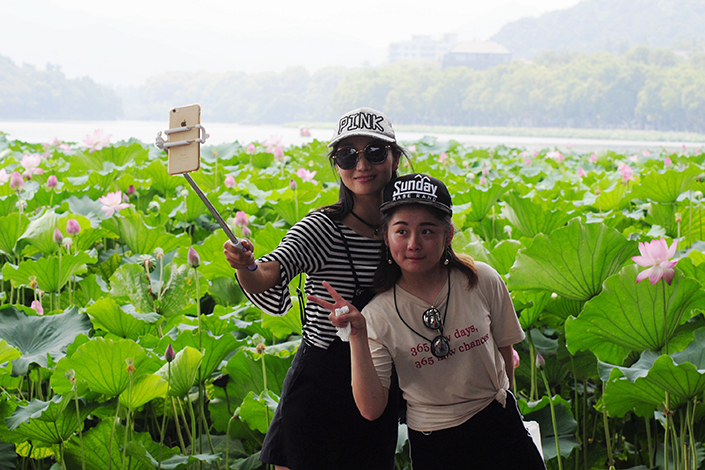 Online travel agency Ctrip is seeking to grow its market share in a tourism market dominated by entrenched offline opponents.  Above, two Hangzhou visitors take a selfie in front of lotus at West Lake in Hangzhou, Zhejiang province, on July 28. Photo: IC