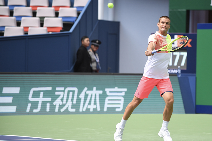 Although LeSports announced in May that it would move some of its operations into Ningbo Ecopark in Zhejiang province within three months, it is unclear if that relocation process has begun. Above, Mikhail Youzhny of Russia plays in front of an advertisement with LeSports' Chinese name, Leshi Tiyu, in Shanghai in October. Photo: IC
