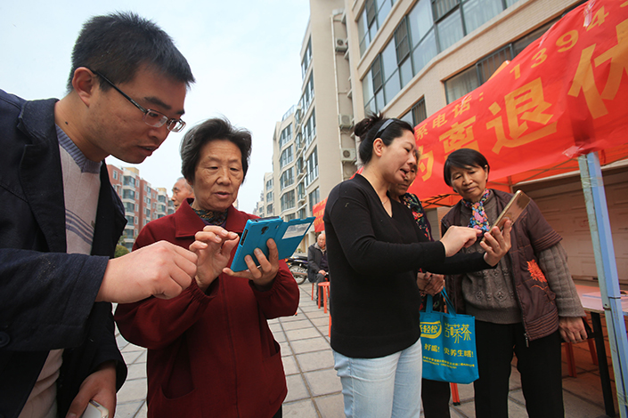 A new report says that 96.3% of internet users in China had access through their cellphones, an increase of 1.2 percentage points from the end of last year. Above, volunteers in Kaifeng, Henan province, demonstrate how to surf the internet on smartphones in April 2016. Photo: IC