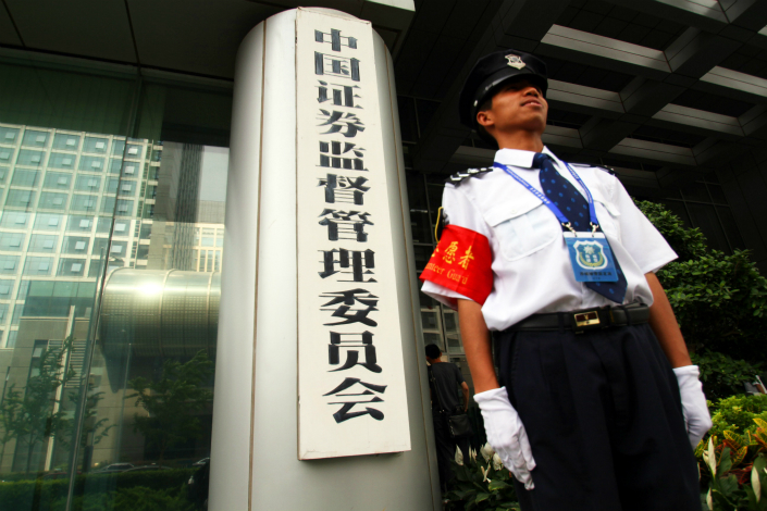 The China Securities Regulatory Commission's latest investigation has uncovered new cases of market manipulation involving large groups of colluders, a spokesperson said Friday. Above, a security guard stands watch at the China Securities Regulatory Commission in Beijing in June 2010. Photo: Visual China