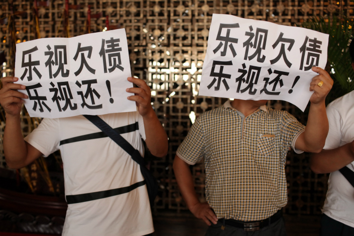 The financially strained tech company LeEco has backed out of a plan to become a founding investor in an insurance company after its many creditors raised objections. Above, some of LeEco's creditors, including suppliers, demonstrate at the company's shareholders meeting on July 17 carrying signs demanding that LeEco pays what it owes them. Photo: IC
