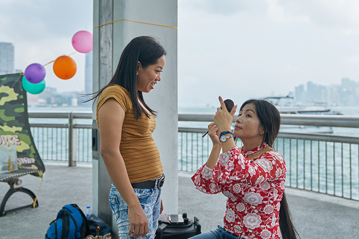 A senior Philippines official recently said he met with Chinese counterparts to discuss five major cities on the Chinese mainland that may soon welcome Filipino domestic workers. Above, two Filipino maids wait for friends at a party in Hong Kong in October. Photo: Visual China