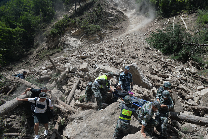 Militia soldiers on Wednesday carry off a person injured in a landslide caused by Tuesday's earthquake in Jiuzhaigou county, Sichuan province. Photo: Visual China